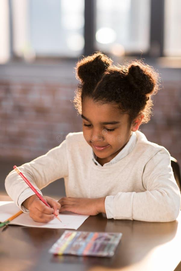 Прелестный маленький студент начальной школы держа карандаш и делая домашнюю работу стоковые изображения