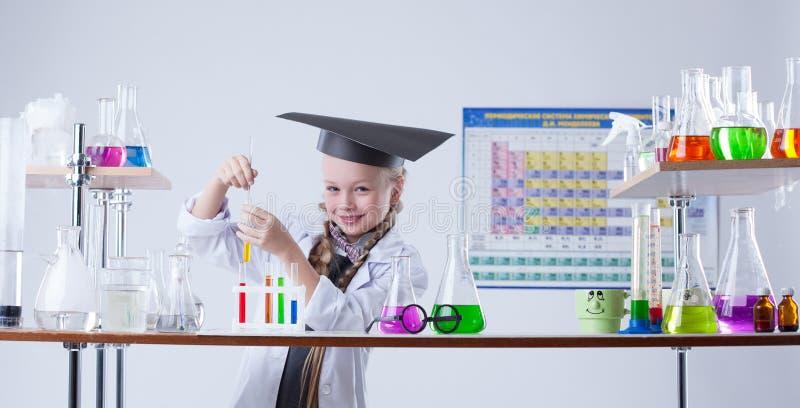 Прелестный маленький химик представляя в лаборатории с склянками стоковые фото