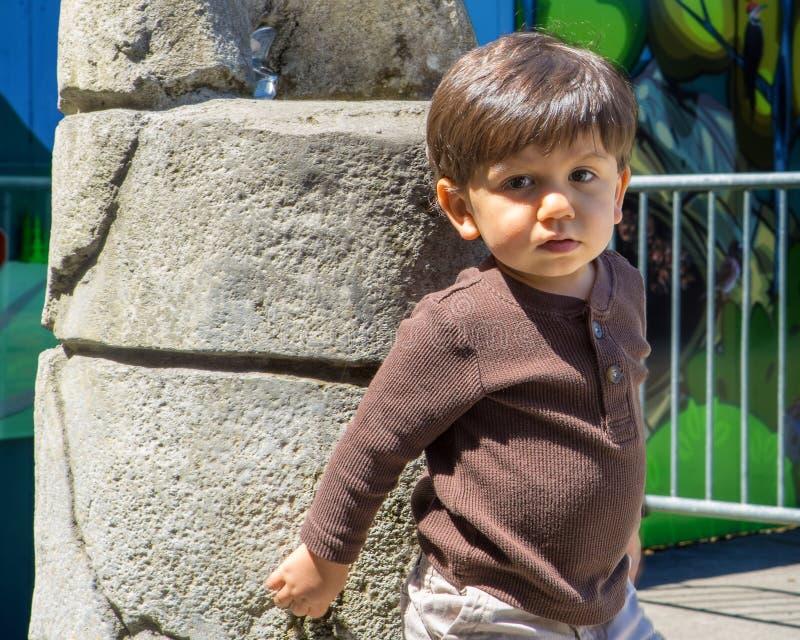 Прелестный малыш полагается против фонтана стоковое изображение