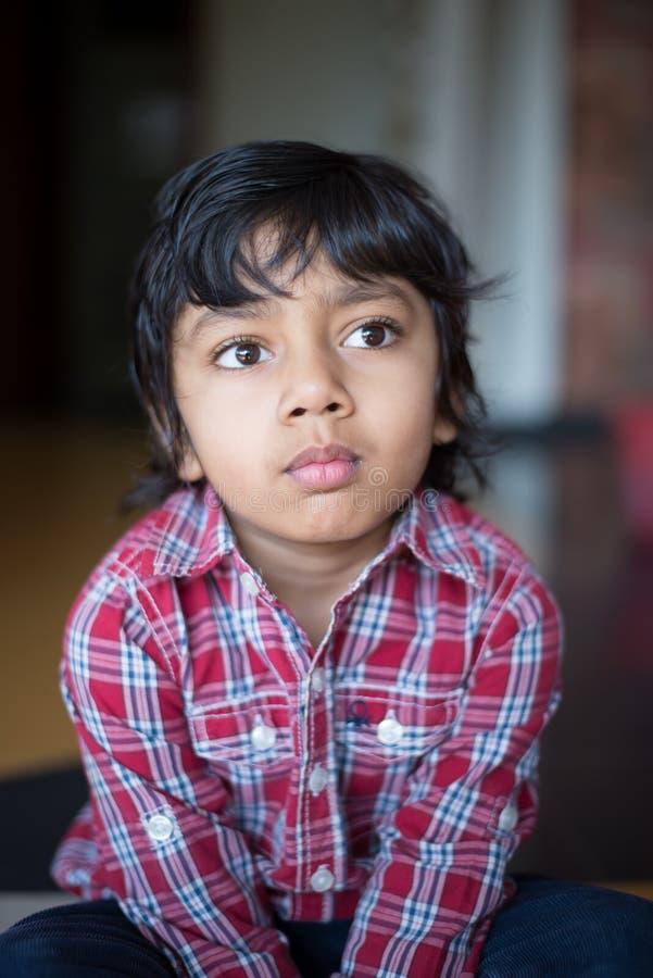 Прелестный мальчик в проверенном ребенке рубашки вытаращить с фокусом и вниманием стоковое изображение