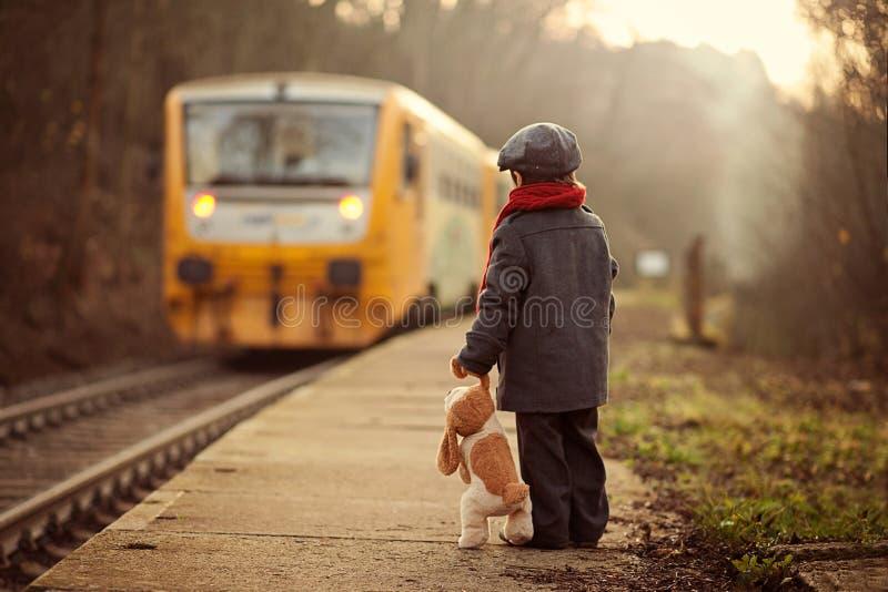 Прелестный мальчик на железнодорожном вокзале, ждать поезд стоковое фото rf
