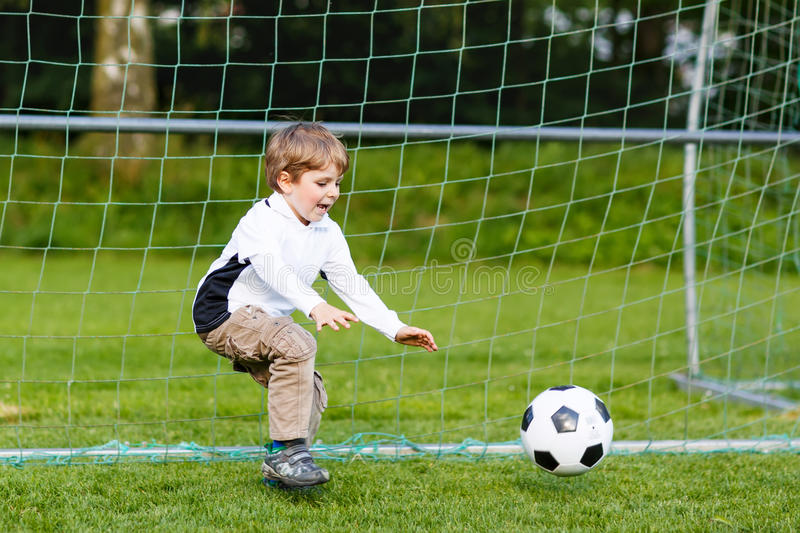 Прелестный милый мальчик маленького ребенка играя футбол и футбол на поле стоковое фото