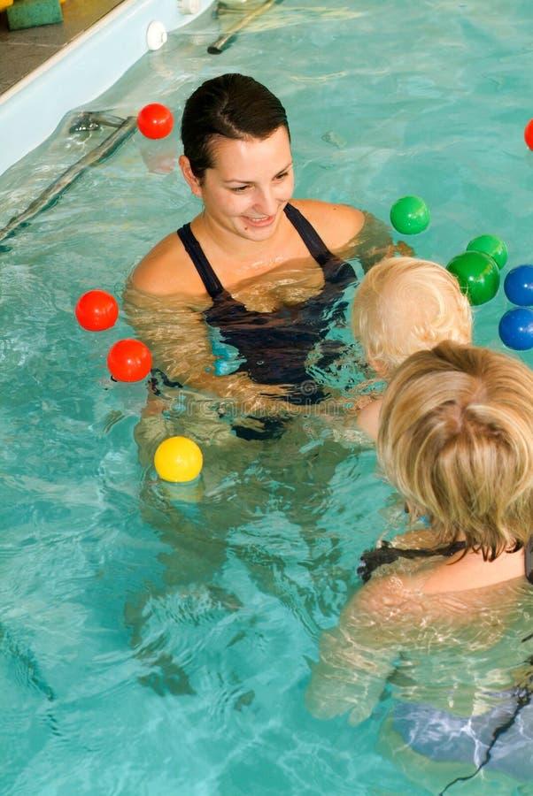 Прелестный младенец наслаждаясь плавать в бассейне с его матерью стоковое фото