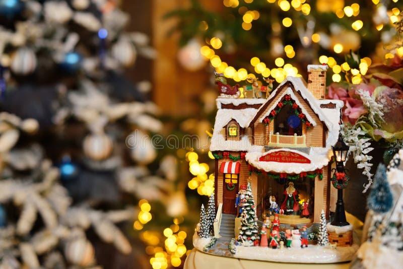 Прелестный дом игрушки музыки рождества с миниатюрным santa представляет украшенную предпосылку bokeh дерева стоковые изображения