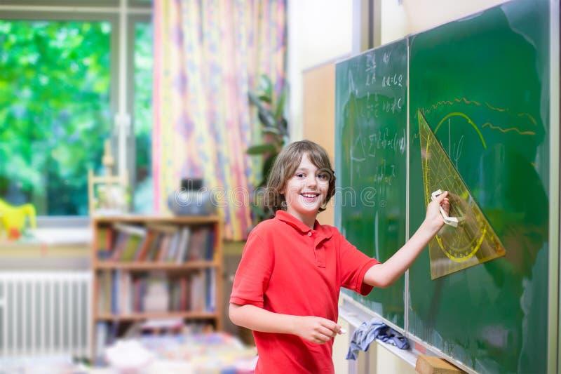Прелестный ребенок школьного возраста на классе математики стоковые фотографии rf