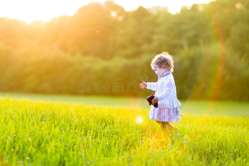 Прелестный ребёнок в поле осени на заходе солнца стоковое изображение