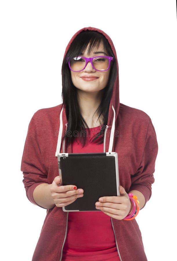 Предназначенная для подростков девушка в красном цвете с таблеткой на белой предпосылке. стоковые фотографии rf