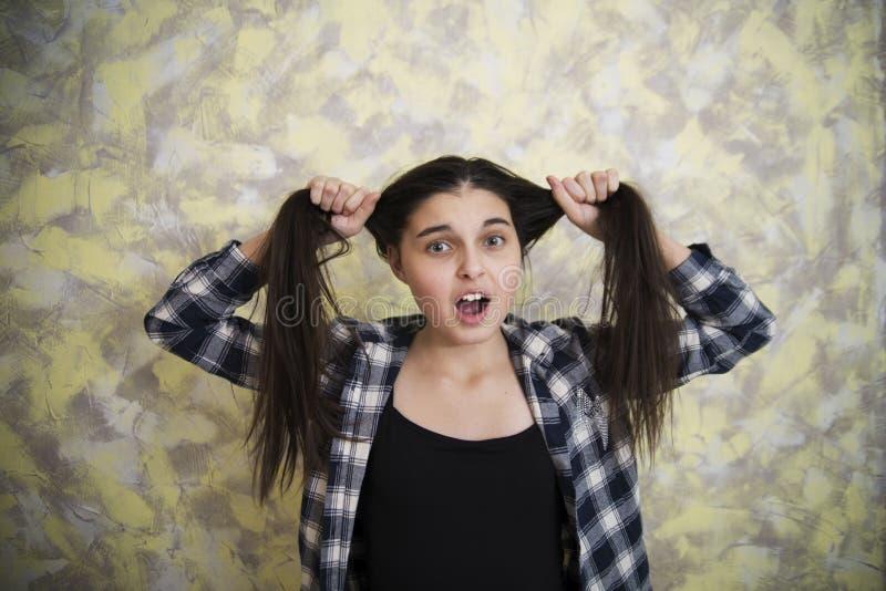 Предназначенная для подростков девушка в рубашке шотландки вытягивая волосы стоковые изображения