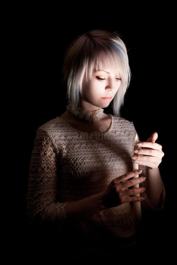 Предназначенная для подростков девушка в темноте с свечой, страх на ее стороне, смотря вниз стоковое фото rf