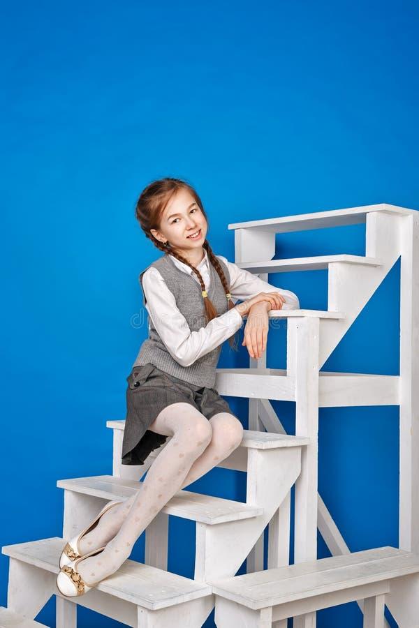 Предназначенная для подростков девушка в школьной форме сидит на шагах стоковые фотографии rf