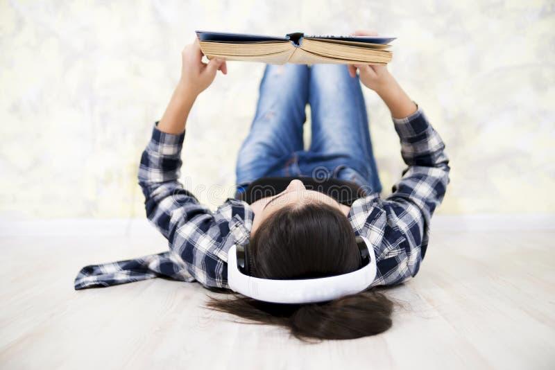 Предназначенная для подростков девушка в шлемофоне читая книгу стоковые фото