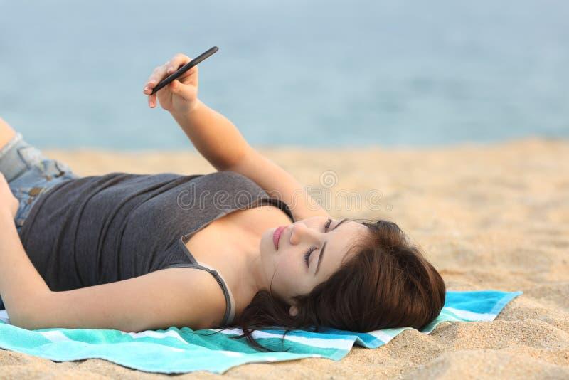 Предназначенная для подростков девушка лежа и используя умный телефон стоковые изображения