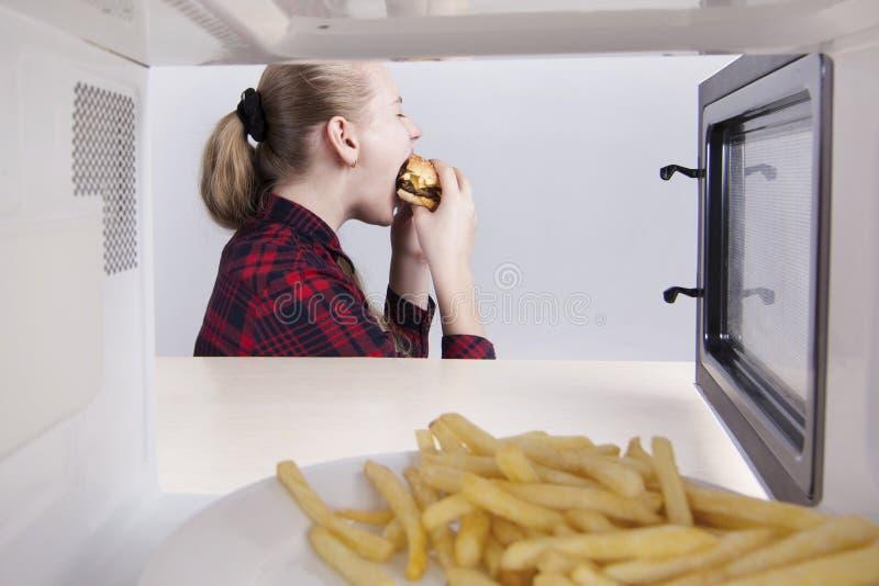 Предназначенная для подростков девушка жадно ест рот гамбургера широко открытый Сидеть на таблице около микроволны Взгляд через о стоковая фотография
