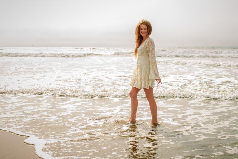 Предназначенная для подростков девушка идя в океан стоковые изображения