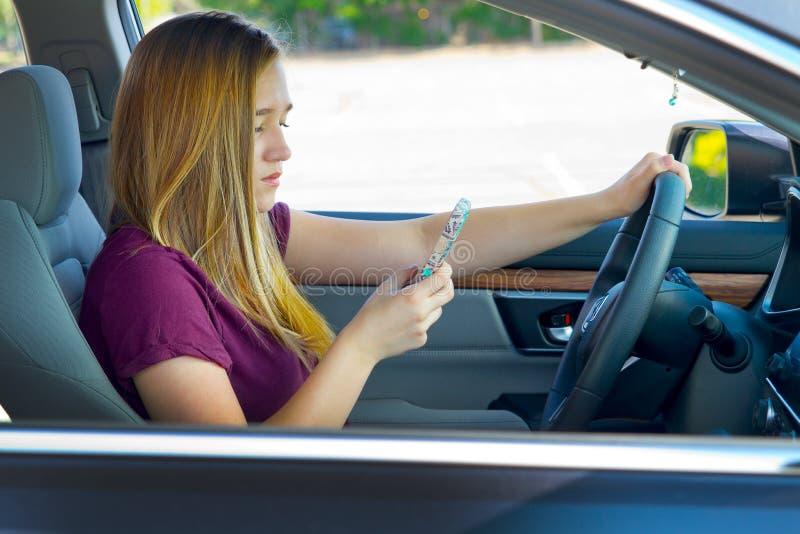 Предназначенная для подростков девушка отправляя СМС и управляя стоковое фото