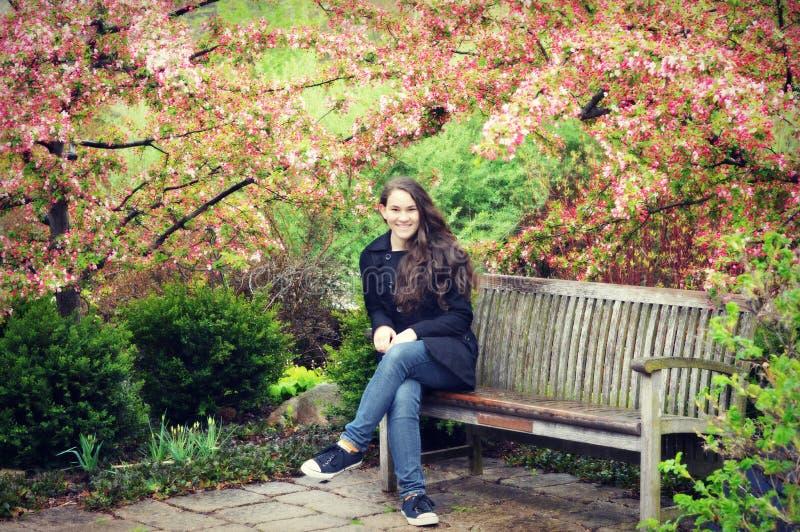 Предназначенная для подростков девушка сидя на стенде с цветениями Яблока краба стоковая фотография