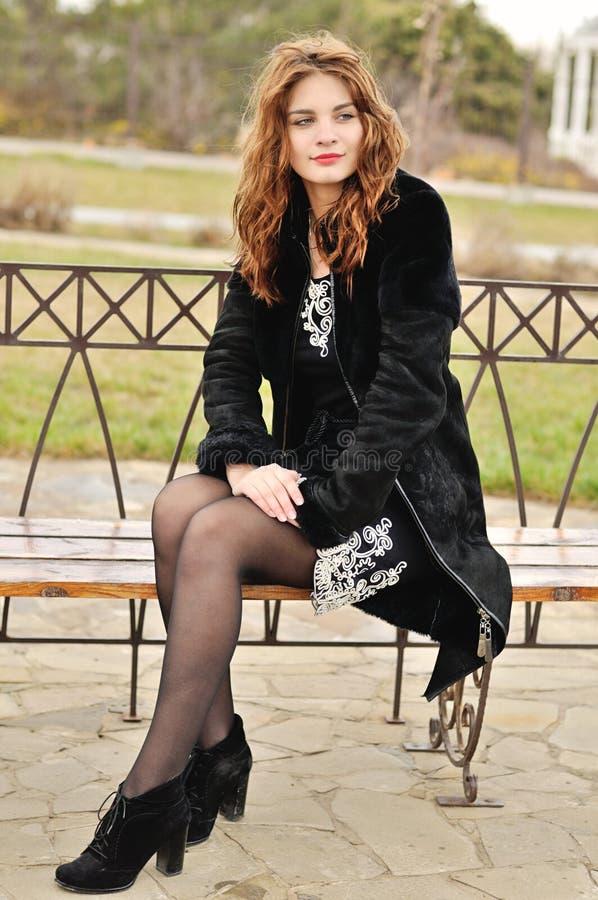 Предназначенная для подростков девушка сидя на стенде стоковые фото