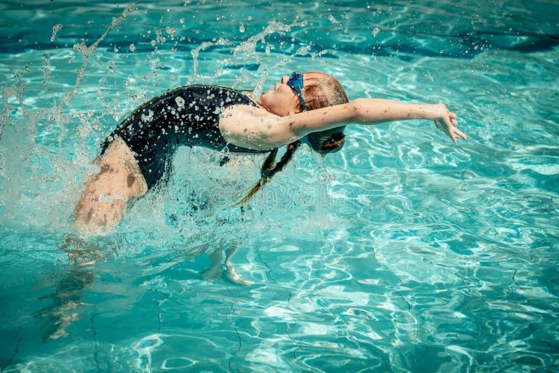 Предназначенная для подростков девушка скача в бассейн стоковая фотография rf
