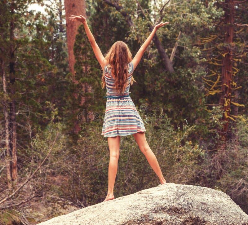 Предназначенная для подростков девушка стоя на большом утесе с открытыми оружиями стоковая фотография rf