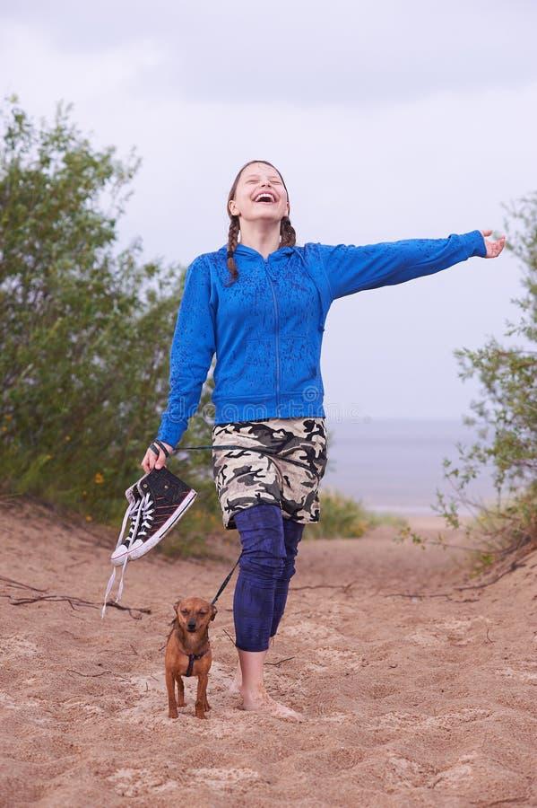 Предназначенная для подростков девушка стоя на пляже с ее собакой стоковая фотография