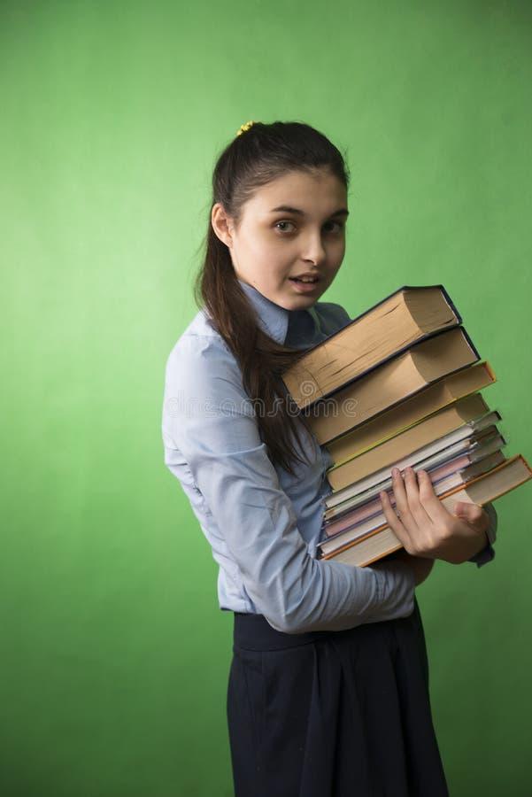 Предназначенная для подростков девушка с стогом книг стоковые фото