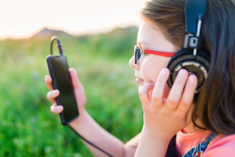Предназначенная для подростков девушка слушая к музыке с ее наушниками внешними стоковое изображение rf