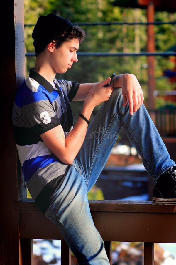 Предназначенная для подростков отправка СМС мальчика стоковые изображения