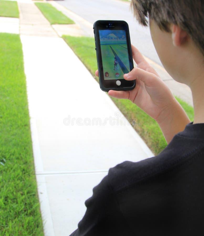Предназначенное для подростков играя Pokemon идет стоковое изображение rf