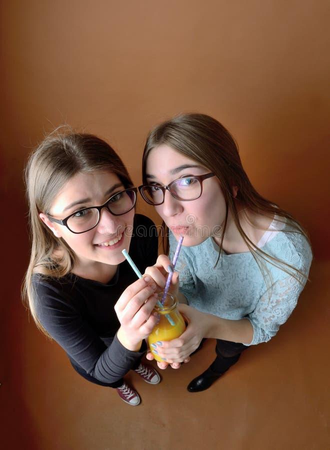 Предназначенные для подростков девушки выпивая совместно стоковая фотография