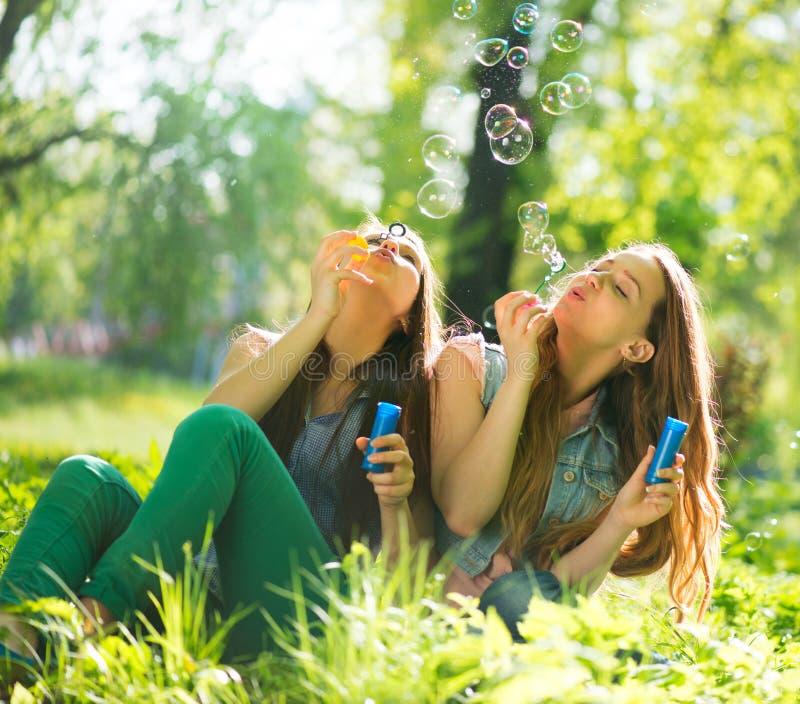 Предназначенные для подростков девушки смеясь над и дуя пузырями мыла стоковые изображения rf