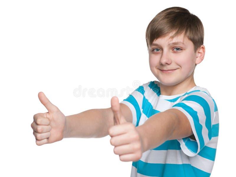 Предназначенный для подростков мальчик держит его большие пальцы руки вверх стоковое изображение rf