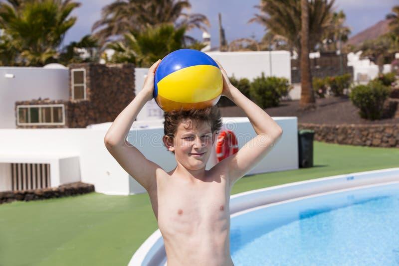 Предназначенный для подростков мальчик при шарик стоя рядом с бассейном стоковые изображения