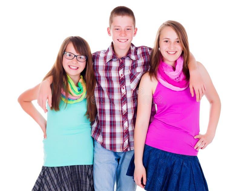 Предназначенный для подростков мальчик стоя с 2 подругами стоковое фото rf