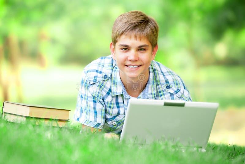 Предназначенный для подростков мальчик с компьтер-книжкой стоковое фото