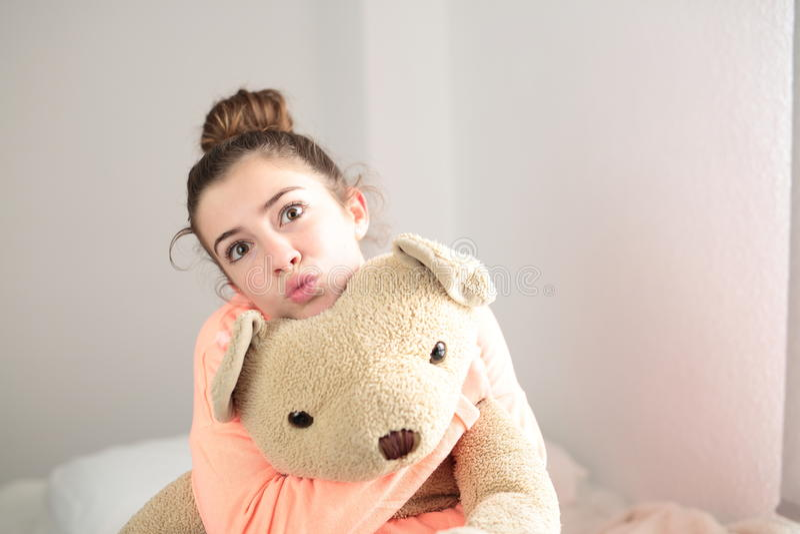 Предназначенный для подростков обнимающ ее плюшевый медвежонка стоковые фото