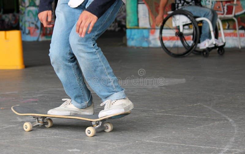 Предназначенный для подростков скейтбордист на доске конька с diabled человеком в кресло-коляске стоковая фотография