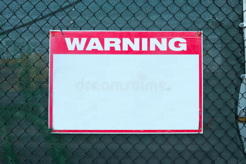 Предосторежение безопасности предупредительного знака с пустым белым сообщением на границе решетки строительной площадки стоковые изображения