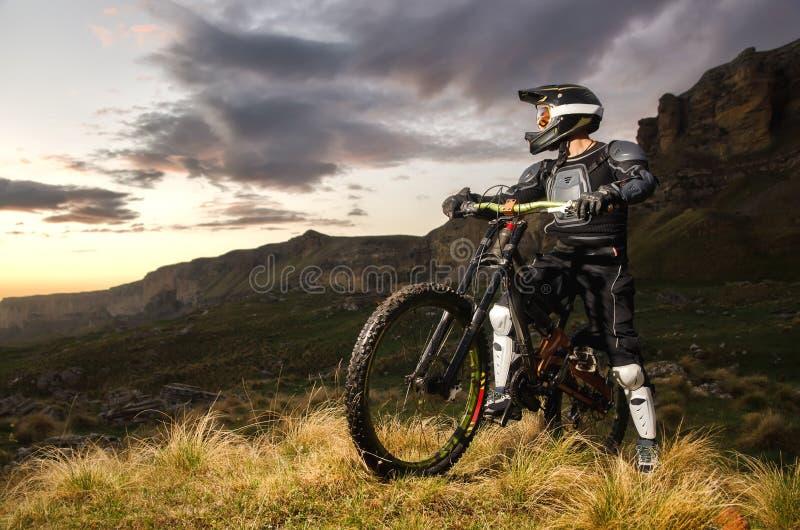 Предохранение от всадника полностью на горном велосипеде стоит и смотрит заход солнца на предпосылке утесов стоковая фотография
