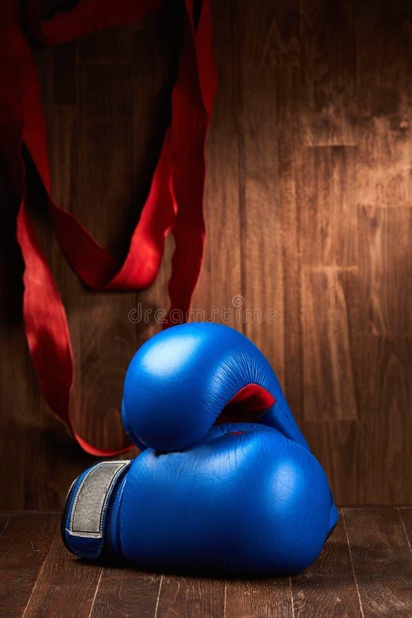 Предпосылка бокса с перчатками и красная повязка против деревянной предпосылки стоковое изображение