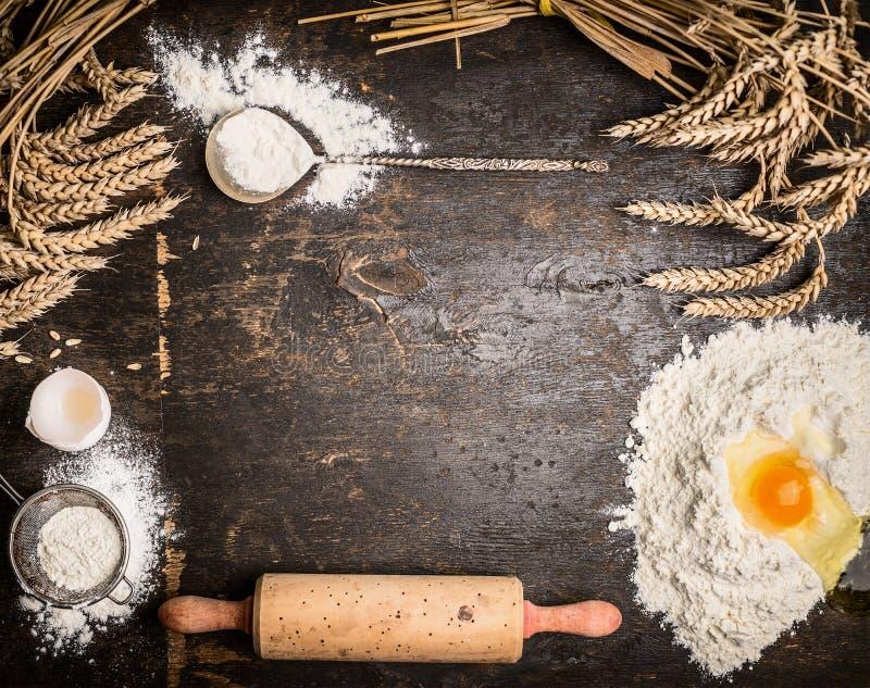 Предпосылка выпечки с печет инструменты, муку, яичко и вращающую ось на деревенской деревянной предпосылке стоковые изображения