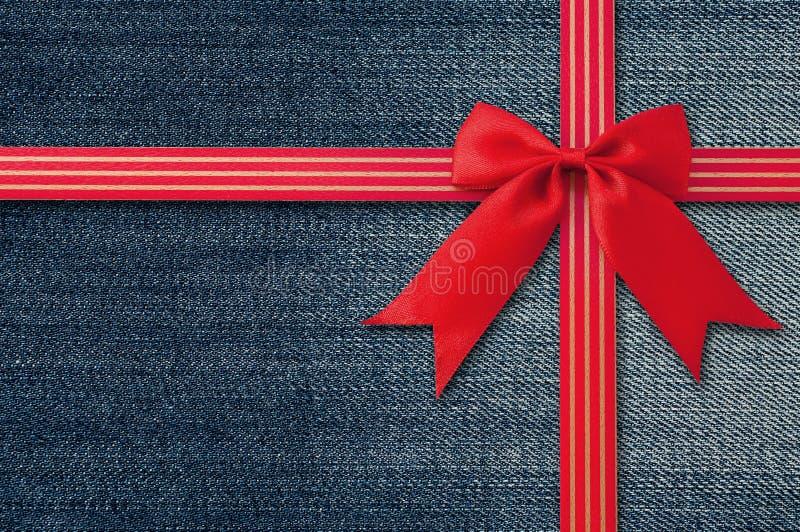 Предпосылка голубых джинсов с красным смычком стоковые изображения