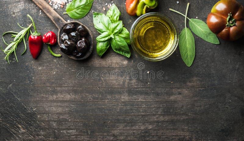 Предпосылка еды с овощами, травами и condiment Греческие черные оливки, свежий базилик, шалфей, розмариновое масло, томат, перцы стоковые фотографии rf