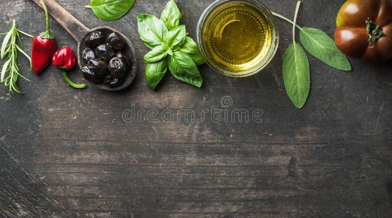 Предпосылка еды с овощами, травами и condiment Греческие черные оливки, свежий базилик, шалфей, розмариновое масло, томат, перцы стоковое фото