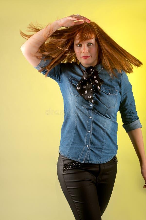 Предпосылка желтого цвета женщины Redhead стоковые фото