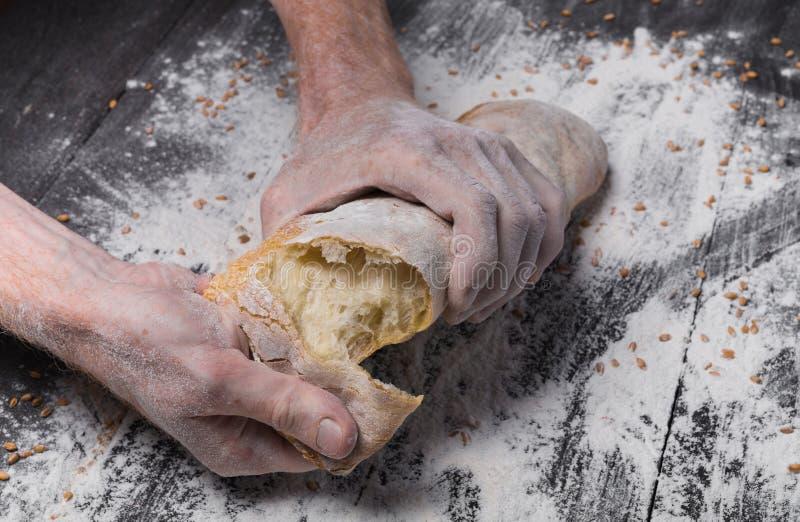 Предпосылка концепции хлебопекарни Руки ломая хлебец хлеба стоковые изображения