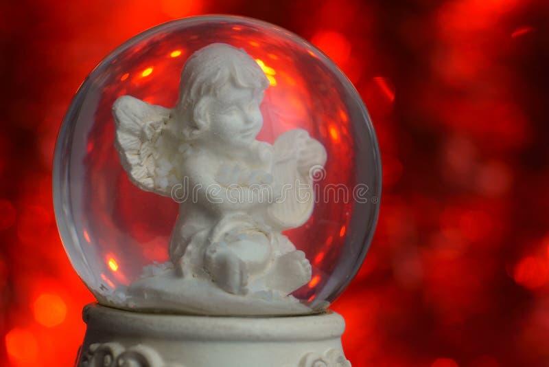 Предпосылка красного цвета шарика снега ангела рождества стоковое изображение rf