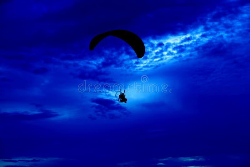 Предпосылка моря захода солнца paramotor силуэта пилотная стоковое фото