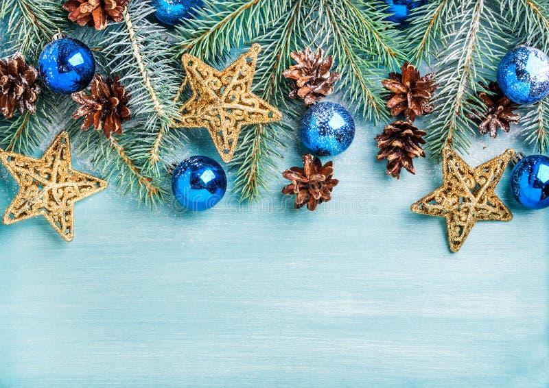 Предпосылка Нового Года или рождества: ель разветвляет, шарики синего стекла, конусы, золотые звезды над фоном бирюзы деревянным стоковое изображение