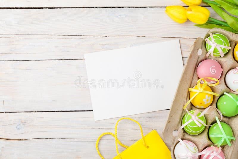 Предпосылка пасхи с красочными яичками и желтыми тюльпанами стоковое фото rf