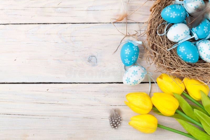 Предпосылка пасхи с красочными яичками и желтыми тюльпанами стоковое изображение